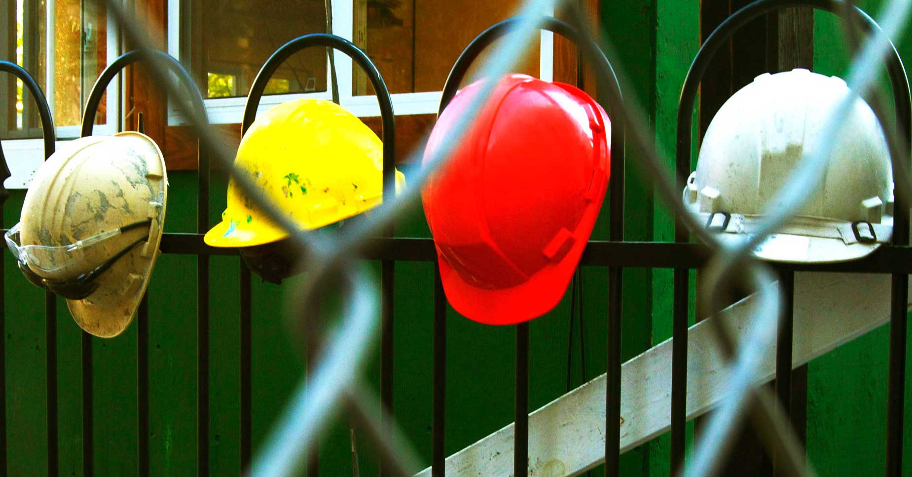 row of hard hats hanging on a fence