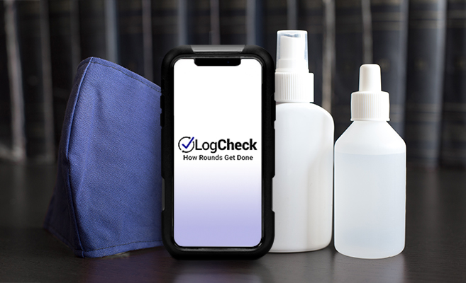 A medical mask, LogCheck app displayed on an iPhone, and disinfectant sprays